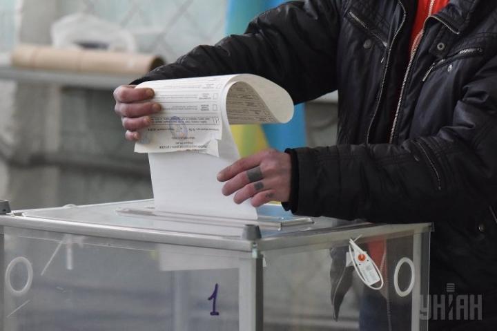 Чоловік вкидає бюлетень в урну для голосування. Фото: УНІАН
